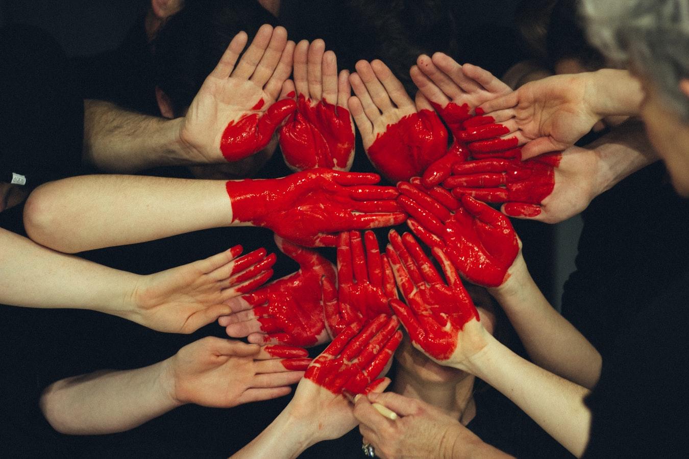 Plusieurs mains rassemblées enduites de peinture rouge dessinant un coeur.